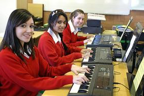 Students playing the piano in music room